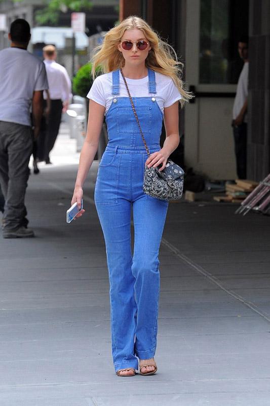Elsa Hosk de paseo en Nueva york con un peto vaquero, camiseta básica y bolso en bandolera.